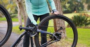 Θηλυκός ποδηλάτης που επισκευάζει το ελαστικό αυτοκινήτου ποδηλάτων απόθεμα βίντεο