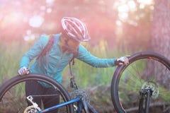 Θηλυκός ποδηλάτης που επισκευάζει το ποδήλατο βουνών Στοκ φωτογραφία με δικαίωμα ελεύθερης χρήσης