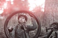 Θηλυκός ποδηλάτης που επισκευάζει το ποδήλατο βουνών Στοκ Φωτογραφίες