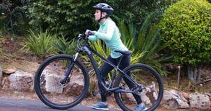 Θηλυκός ποδηλάτης που περπατά με το ποδήλατο βουνών στο δάσος απόθεμα βίντεο