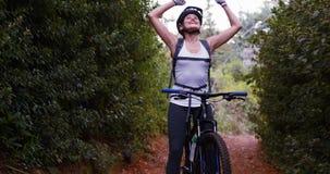 Θηλυκός ποδηλάτης που στέκεται με το ποδήλατο βουνών φιλμ μικρού μήκους