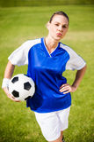Θηλυκός ποδοσφαιριστής που στέκεται με μια σφαίρα Στοκ εικόνες με δικαίωμα ελεύθερης χρήσης