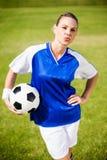 Θηλυκός ποδοσφαιριστής που στέκεται με μια σφαίρα Στοκ Εικόνες