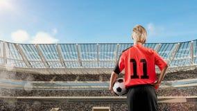 Θηλυκός ποδοσφαιριστής που στέκεται με τη σφαίρα ενάντια στο συσσωρευμένο στάδιο στο υπόβαθρο Στοκ Φωτογραφίες