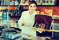 Θηλυκός πωλητής που προσφέρει το μεγάλο κιβώτιο των σοκολατών Στοκ εικόνες με δικαίωμα ελεύθερης χρήσης