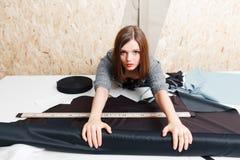 Θηλυκός ράφτης που παίρνει το ύφασμα για την κοπή σχεδίων Στοκ Εικόνες
