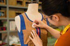 Θηλυκός ράφτης σχεδίου ιματισμού που εργάζεται στο ομοίωμα Στοκ φωτογραφία με δικαίωμα ελεύθερης χρήσης