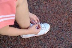 Θηλυκός δρομέας που δένει το αθλητικό παπούτσι της στοκ εικόνα