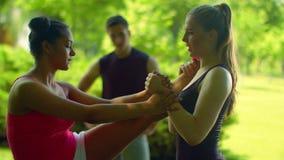 Θηλυκός δρομέας που κάνει την τεντώνοντας άσκηση Τέντωμα φίλων Multiethnic υπαίθριο απόθεμα βίντεο