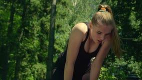 Θηλυκός δρομέας που στηρίζεται μετά από να τρέξει σκληρά στηργμένος κουρασμένη γυναίκα απόθεμα βίντεο
