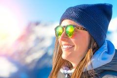 Θηλυκός σκιέρ με τα σκι που χαμογελούν και που φορούν τα γυαλιά σκι Στοκ Εικόνα