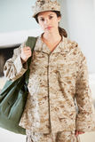 Θηλυκός στρατιώτης με το σπίτι τσαντών εξαρτήσεων για την άδεια Στοκ Εικόνες