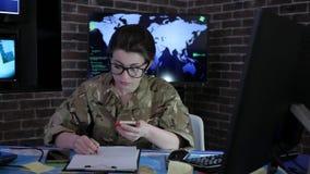 Θηλυκός στρατιώτης πορτρέτου με το κινητό τηλέφωνο, κέντρο ελέγχου, πόλεμος απόθεμα βίντεο