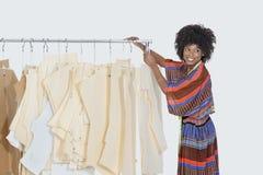 Θηλυκός σχεδιαστής αφροαμερικάνων με το ράψιμο των σχεδίων στο ράφι ενδυμάτων πέρα από το γκρίζο υπόβαθρο στοκ φωτογραφία