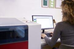 Θηλυκός σχεδιαστής που ενεργοποιεί το σύστημα CAD για τον κόπτη λέιζερ στοκ εικόνες