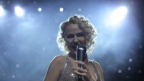 Θηλυκός τραγουδιστής αναδρομικά φωτισμένος στο καπνώές στάδιο φιλμ μικρού μήκους