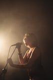 Θηλυκός τραγουδιστής που αποδίδει στο φωτισμένο νυχτερινό κέντρο διασκέδασης Στοκ φωτογραφία με δικαίωμα ελεύθερης χρήσης