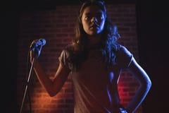 Θηλυκός τραγουδιστής που στέκεται ενάντια στον τοίχο στο νυχτερινό κέντρο διασκέδασης Στοκ Φωτογραφίες
