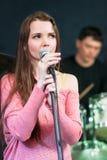 Θηλυκός τραγουδιστής στο ρόδινο φόρεμα κοντά στο μικρόφωνο Στοκ εικόνα με δικαίωμα ελεύθερης χρήσης