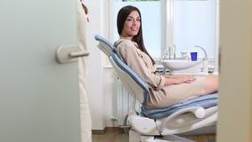 Θηλυκός υπομονετικός οδοντίατρος χαιρετισμού καθμένος στην οδοντική καρέκλα απόθεμα βίντεο