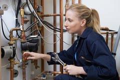 Θηλυκός υδραυλικός που εργάζεται στο λέβητα κεντρικής θέρμανσης Στοκ φωτογραφία με δικαίωμα ελεύθερης χρήσης