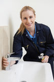 Θηλυκός υδραυλικός που εργάζεται στο νεροχύτη που χρησιμοποιεί το γαλλικό κλειδί Στοκ εικόνες με δικαίωμα ελεύθερης χρήσης