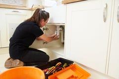 Θηλυκός υδραυλικός που καθορίζει έναν νεροχύτη κουζινών Στοκ εικόνα με δικαίωμα ελεύθερης χρήσης