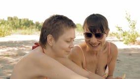 Θηλυκός φίλος που μιλά και που έχει τη διασκέδαση στην παραλία φιλμ μικρού μήκους