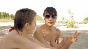 Θηλυκός φίλος που μιλά και που έχει τη διασκέδαση στην παραλία απόθεμα βίντεο