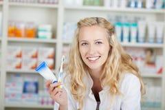 Θηλυκός φαρμακοποιός με την οδοντόπαστα και την οδοντόβουρτσα στοκ εικόνα με δικαίωμα ελεύθερης χρήσης