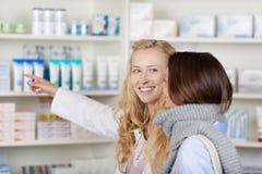 Θηλυκός φαρμακοποιός που δείχνει στα φάρμακα εξετάζοντας Custume στοκ φωτογραφία με δικαίωμα ελεύθερης χρήσης