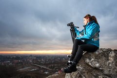 Θηλυκός φωτογράφος με τη κάμερα στο τρίποδο στο μεγάλο βράχο Στοκ εικόνα με δικαίωμα ελεύθερης χρήσης