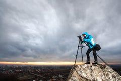 Θηλυκός φωτογράφος με τη κάμερα στο τρίποδο στο μεγάλο βράχο Στοκ εικόνες με δικαίωμα ελεύθερης χρήσης
