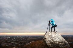 Θηλυκός φωτογράφος με τη κάμερα στο τρίποδο στο μεγάλο βράχο Στοκ Φωτογραφία
