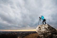 Θηλυκός φωτογράφος με τη κάμερα στο τρίποδο στο μεγάλο βράχο Στοκ φωτογραφίες με δικαίωμα ελεύθερης χρήσης