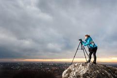 Θηλυκός φωτογράφος με τη κάμερα στο τρίποδο στο μεγάλο βράχο Στοκ Εικόνα