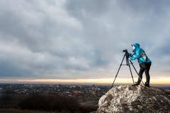 Θηλυκός φωτογράφος με τη κάμερα στο τρίποδο στο μεγάλο βράχο Στοκ Εικόνες