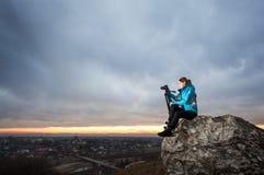 Θηλυκός φωτογράφος με τη κάμερα στο τρίποδο στο μεγάλο βράχο Στοκ φωτογραφία με δικαίωμα ελεύθερης χρήσης