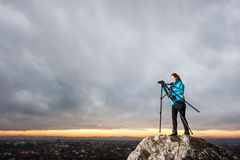 Θηλυκός φωτογράφος με τη κάμερα στο τρίποδο στο μεγάλο βράχο Στοκ Φωτογραφίες