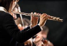 Θηλυκός φλαουτίστας με την ορχήστρα στη σκηνή στοκ εικόνες