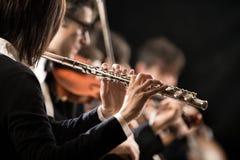 Θηλυκός φλαουτίστας με την ορχήστρα στη σκηνή στοκ φωτογραφία με δικαίωμα ελεύθερης χρήσης