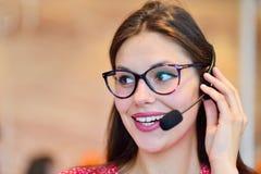 Θηλυκός χειριστής υποστήριξης πελατών με την κάσκα και το χαμόγελο Στοκ Φωτογραφίες