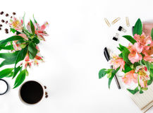 Θηλυκός χώρος εργασίας με τα εξαρτήματα, τον καφέ και την ανθοδέσμη γραφείων Στοκ Φωτογραφίες