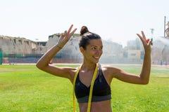 Θηλυκός ψεκασμένος νερό αθλητής sportswear που επιλύει δημόσια το υπαίθριο αθλητικό στάδιο Στοκ Φωτογραφίες