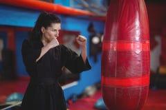 Θηλυκός karate εγκιβωτισμός άσκησης φορέων με punching την τσάντα Στοκ φωτογραφία με δικαίωμα ελεύθερης χρήσης