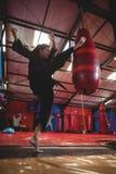 Θηλυκός karate εγκιβωτισμός άσκησης φορέων με punching την τσάντα Στοκ Εικόνα