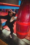 Θηλυκός karate εγκιβωτισμός άσκησης φορέων με punching την τσάντα Στοκ Εικόνες