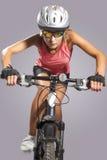 Θηλυκό ανακύκλωσης ποδήλατο βουνών αθλητών οδηγώντας και εξοπλισμένος με τις δημόσιες σχέσεις Στοκ φωτογραφία με δικαίωμα ελεύθερης χρήσης