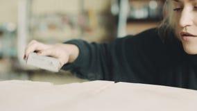 Θηλυκό γυαλίζοντας ξύλο ξυλουργών στο εργαστήριο απόθεμα βίντεο
