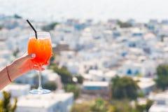 Θηλυκό γυαλί εκμετάλλευσης χεριών με το υπόβαθρο ποτών οινοπνεύματος Spritz Aperol στην όμορφη παλαιά Μύκονο στην Ελλάδα Στοκ φωτογραφίες με δικαίωμα ελεύθερης χρήσης